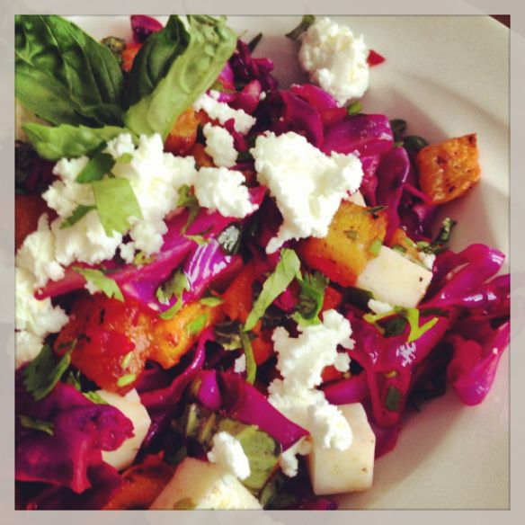 Spicy chile-lime red cabbage & butternut squash salad, with garlic scapes, fresh cilantro, basil and double goat's cheese.