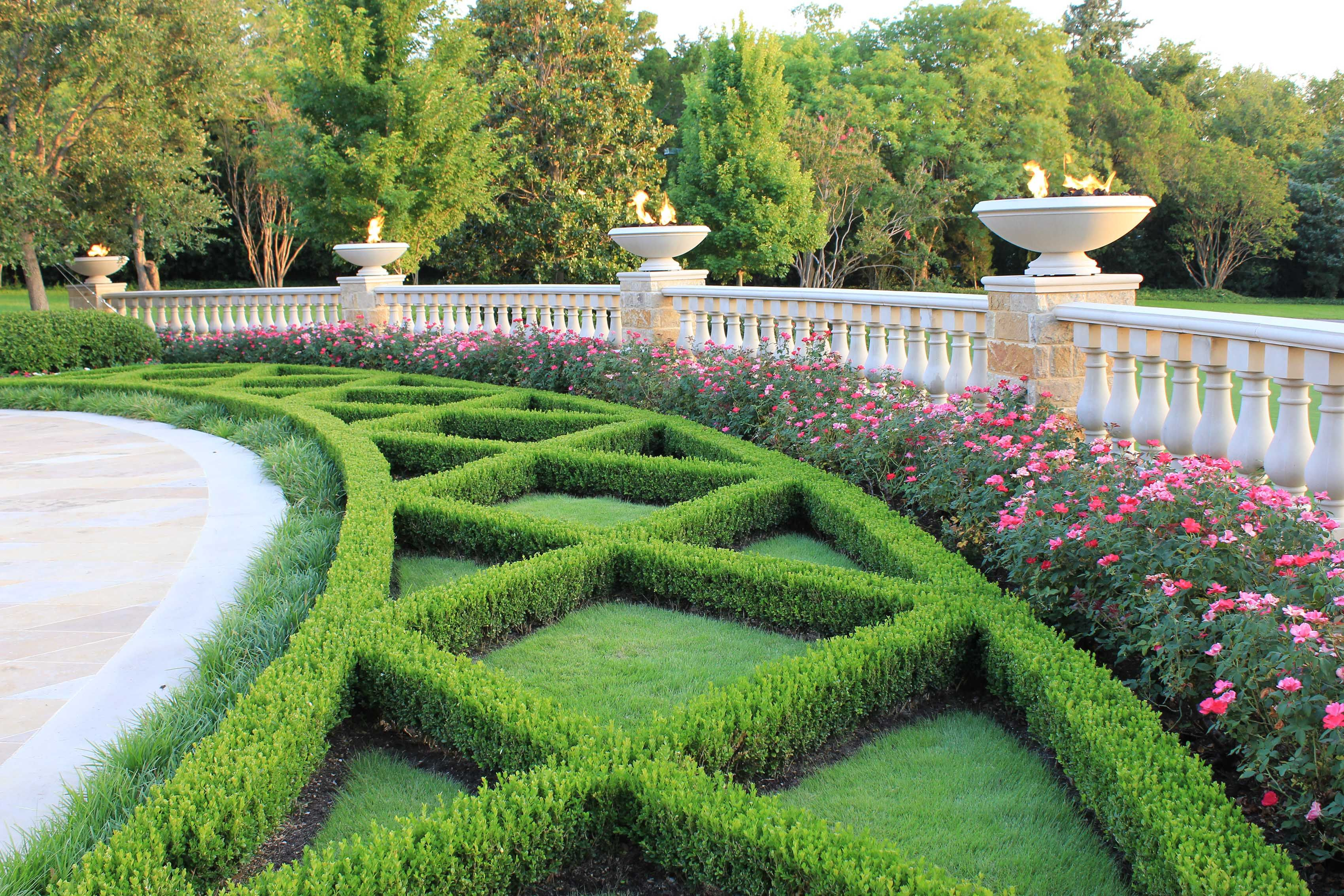 Classic boxwood hedges framed by cast stone ballustrade and fire bowls.  Harold Leidner Landscape Architect, Dallas, Texas