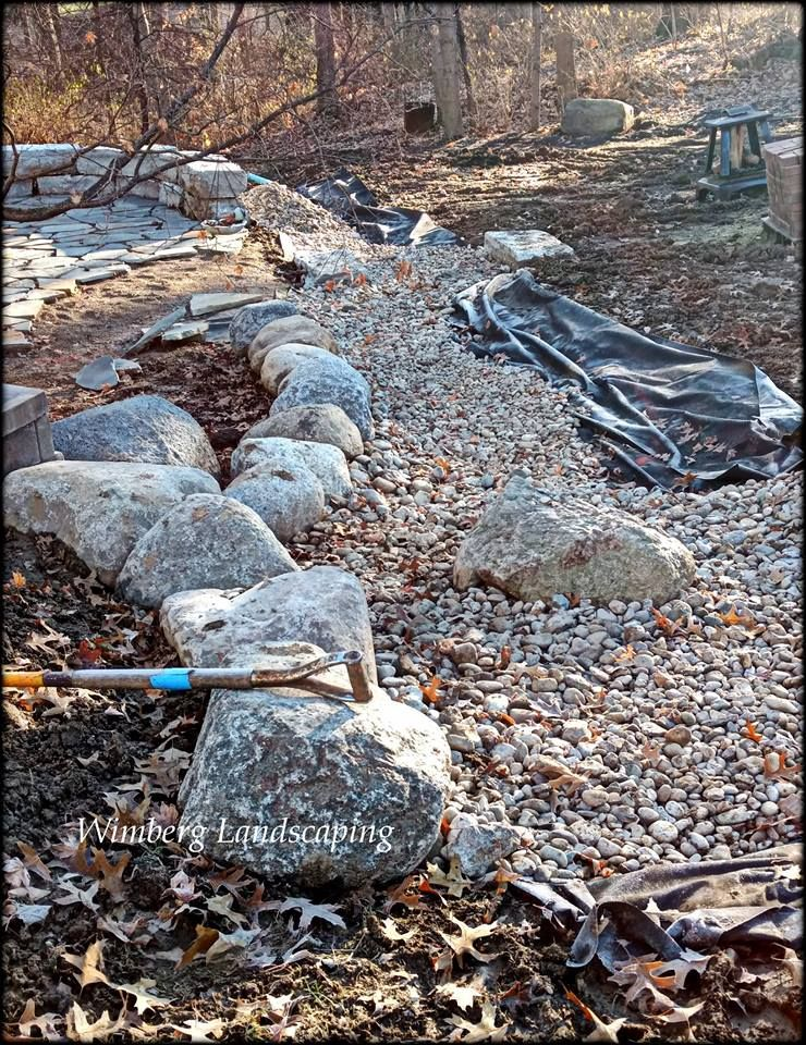 This Complete Backyard Redesign Is Incorporating A Lot Of Stone Elements A Stone Patio Wall And Now A Dry Creek Bed With Images Lawn Maintenance Patio Stones Creek Bed