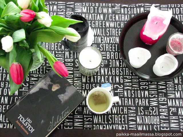 Flowers, candles, a book and a cup of tea