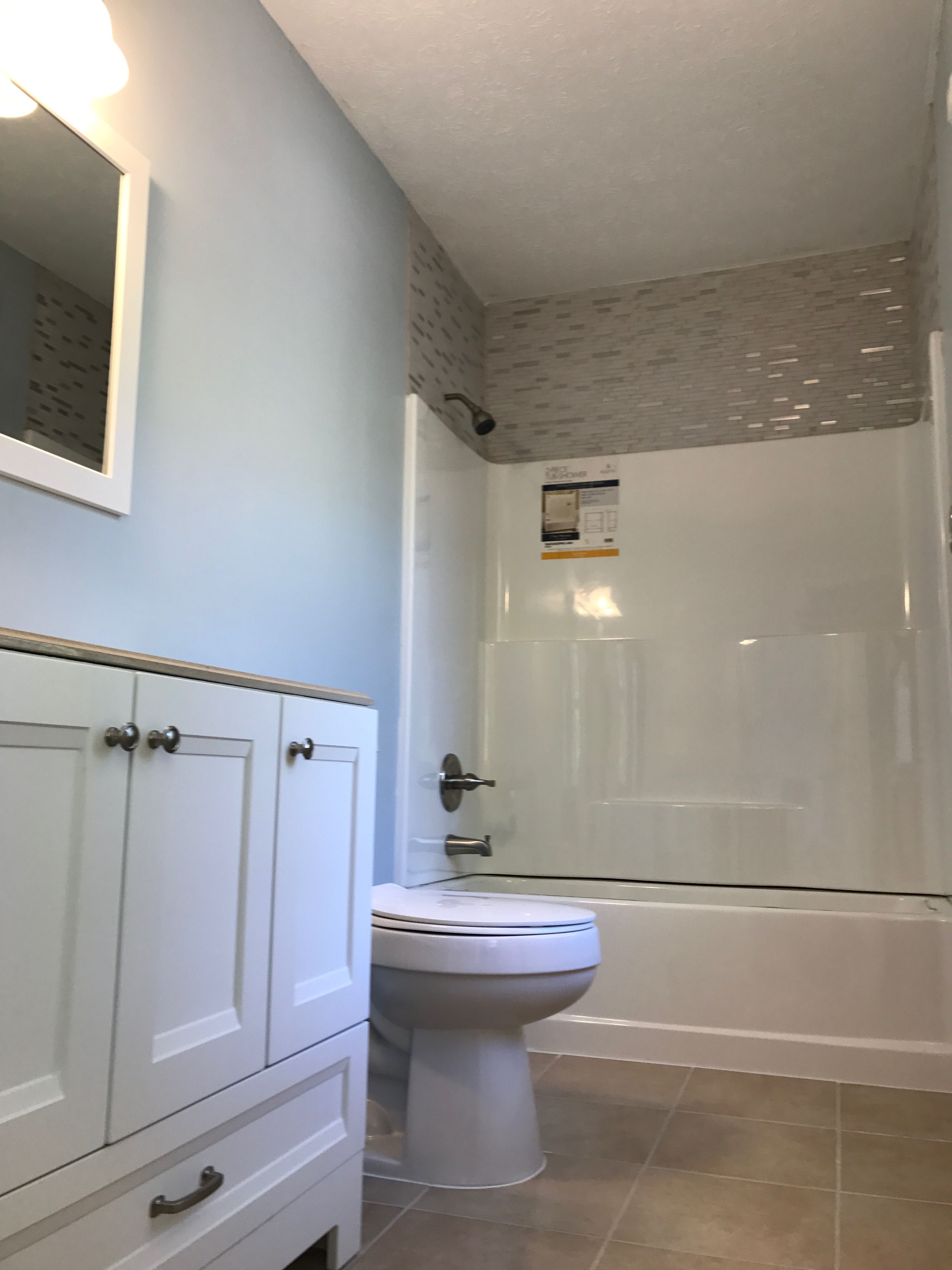 Using glass tile above the tub in a small dark bathroom provides a