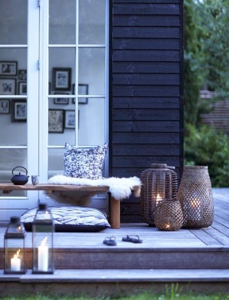 black paint, faded cedar deck, with warm wood tones ... LOVE the lanterns, the combo of the rectangular glass/metal with the oversized willow/reed basket hurricane lanterns in different sizes/shapes/styles of weaving