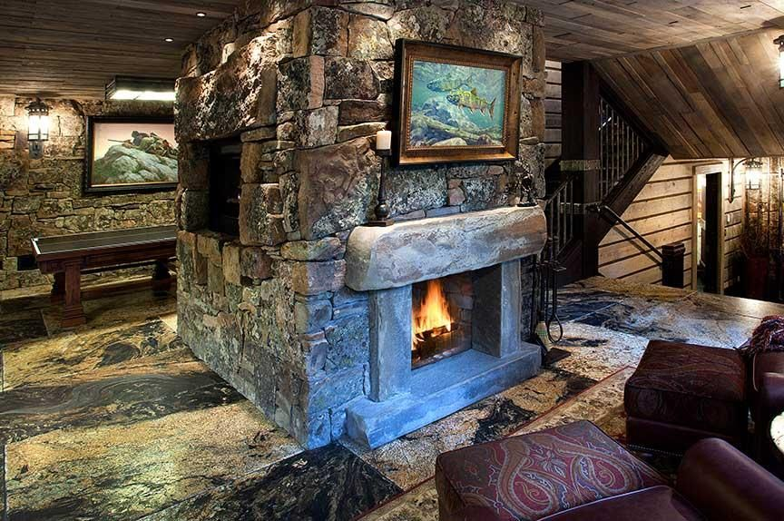 A Stone Column That Features A Double Sided Fireplace And Nook For A Flat Screen Television Craftily Divides The Stone Mansion Expensive Houses Home Fireplace