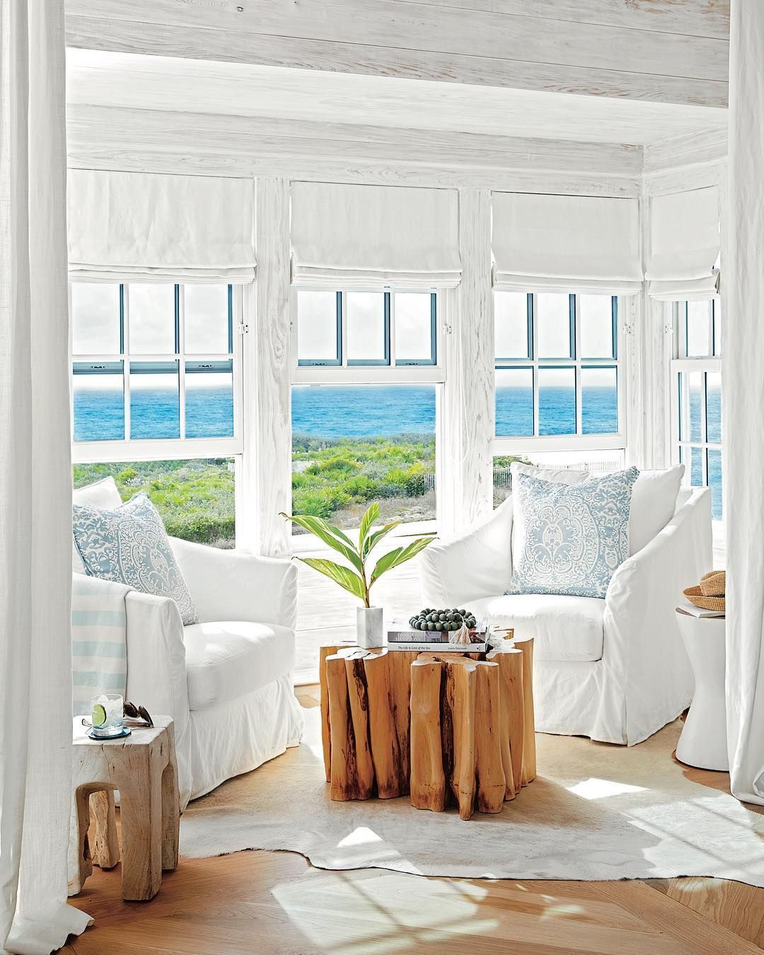 Simple White Clean Seating With Driftwood Tables In This Beach House Decor Coastal Living Rooms Beach House Interior Design Beach House Interior