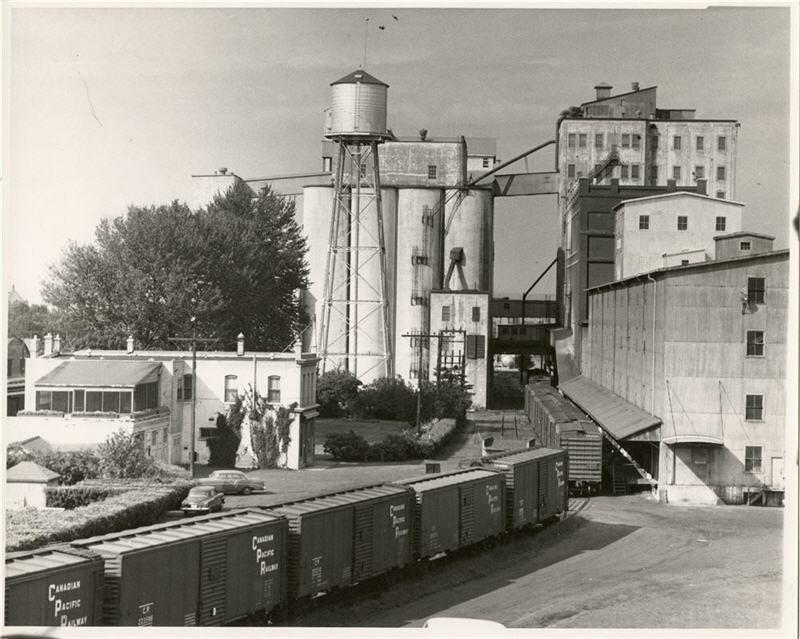 A Cpr Train Passes By Saskatchewan Wheat Pool Grain Elevator 8 Former Ogilvie Flour Mill Late 1950s Elevation Train Grains