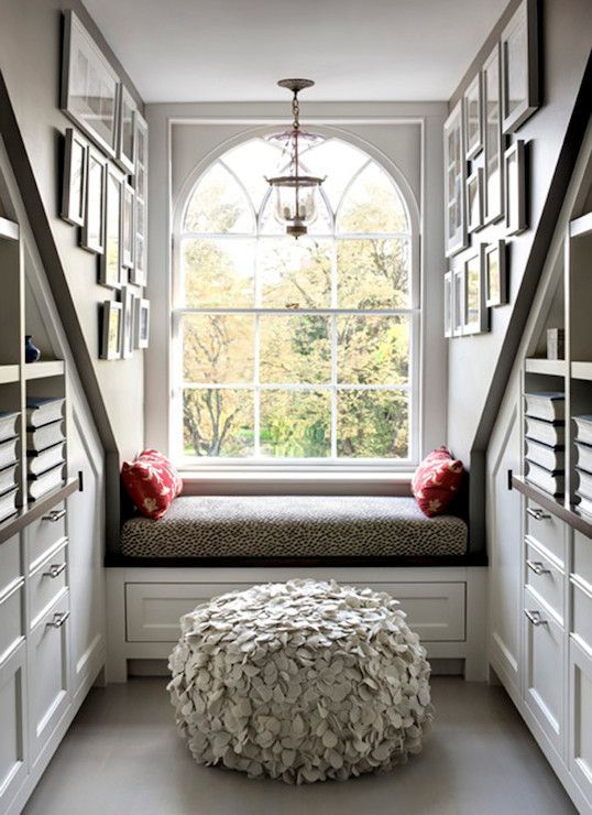 gorgeous bedroom nook with arched dormer window highlighted by a glass lantern over a builtin window seat with storage builtin bookcase cubbies and