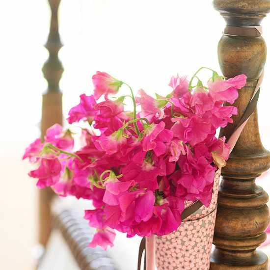 roll decorative paper into a cone and secure with tape. Tuck a small plastic cup inside, and fill with water and pretty sweet peas for a paper basket of flowers