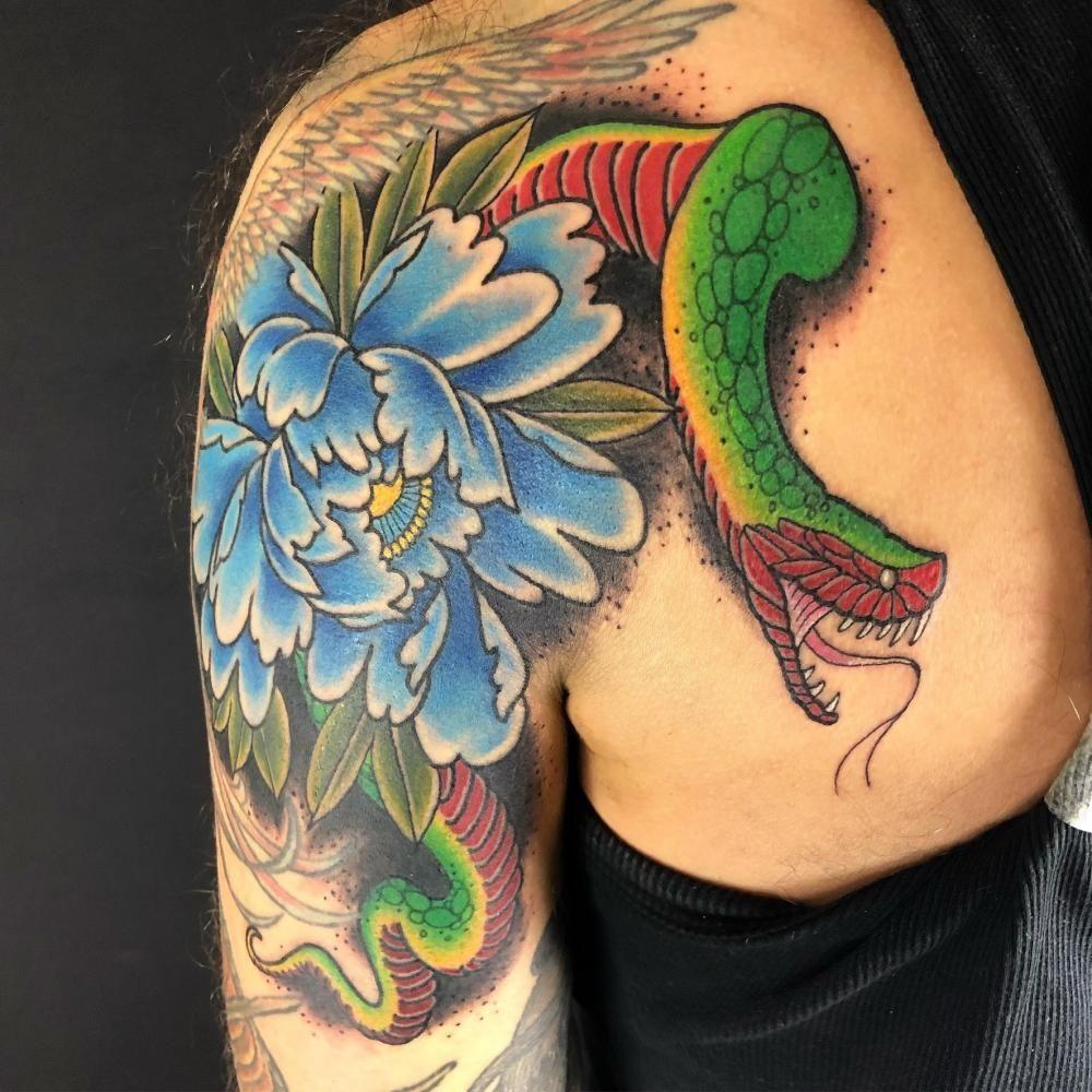 Snake Tattoo with beautiful flower. #SnakeTattoos #TattoosOfSnakes #SnakeTattooIdeas #Snakes #Tattooideas #TattooAwards
