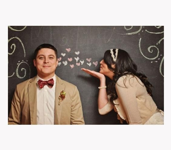 Eager guests can draw cute pictures and scribble messages for the happy couple on a chalkboard backdrop.