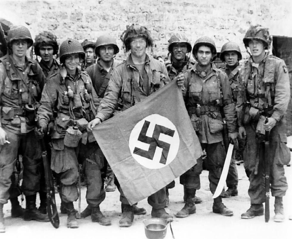 Paratrooper of US 101st Airborne Division holding a Nazi German flag captured in a village near Utah Beach, Saint-Marcouf, France, 8 Jun 1944.