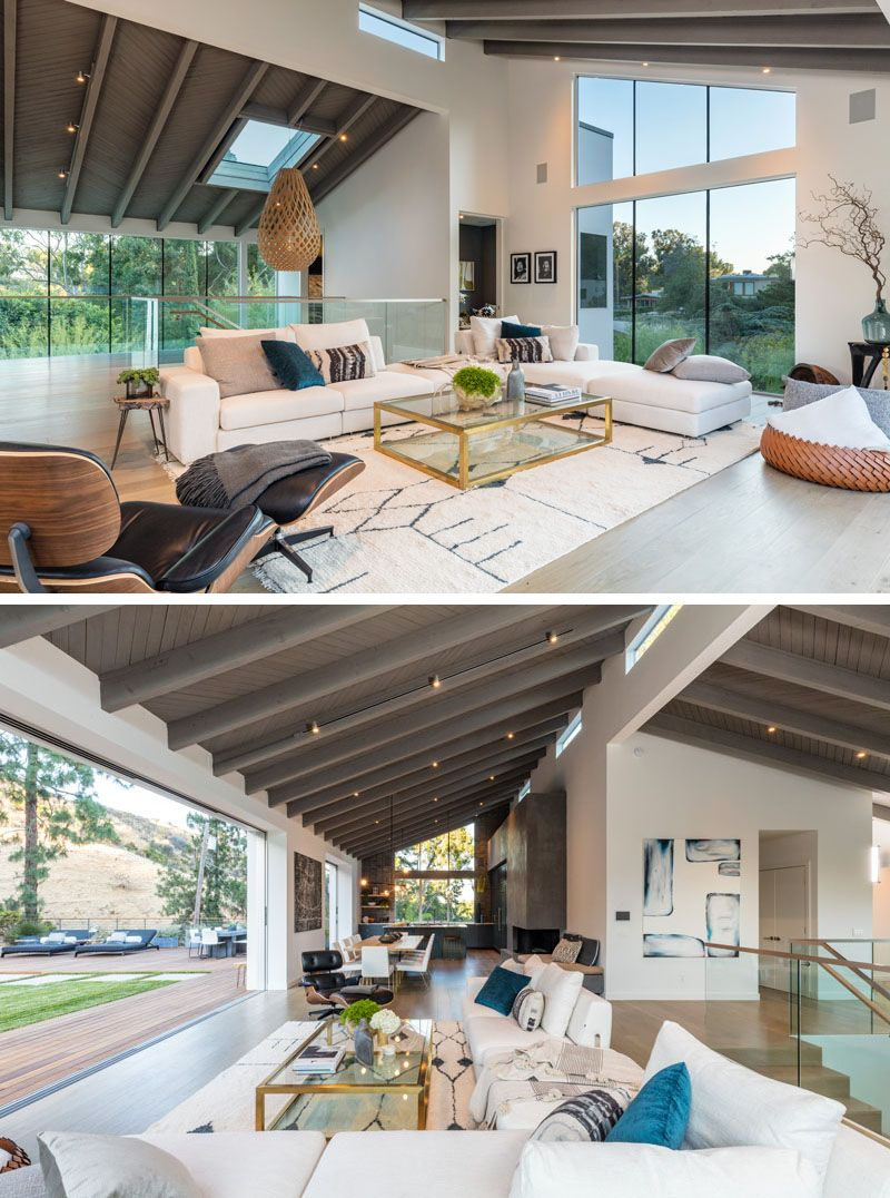 This large and open modern interior features a vaulted ceiling plenty of windows while white oak flooring and a wall of glass that opens to the backyard