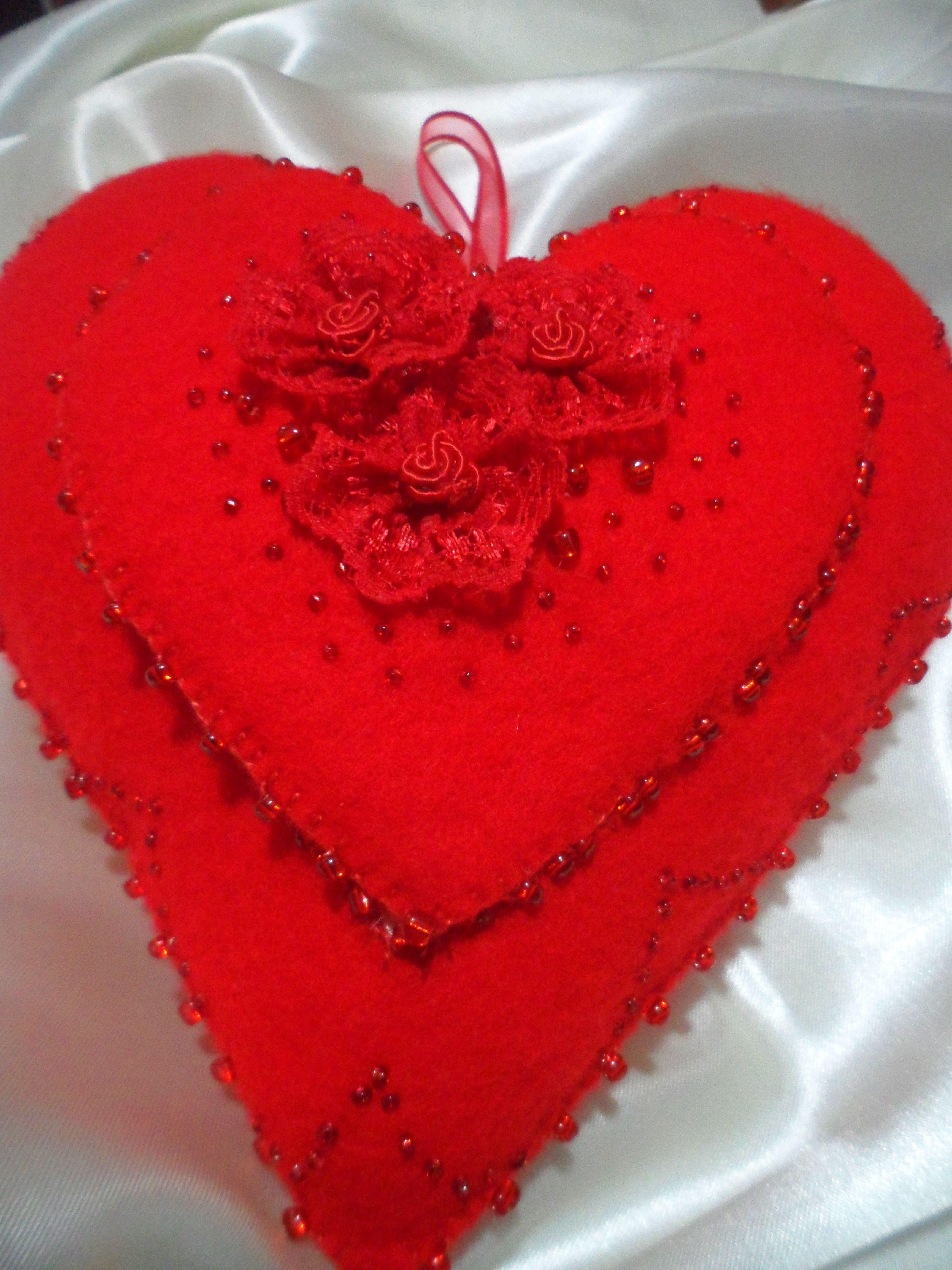 Corazón realizado en Fieltro con un corazón en el medio que se abre y deja ver una frase dedicatoria especial pintada en tela raso, decorado con rosas de puntilla de encaje, mostacillones y mostacillas.