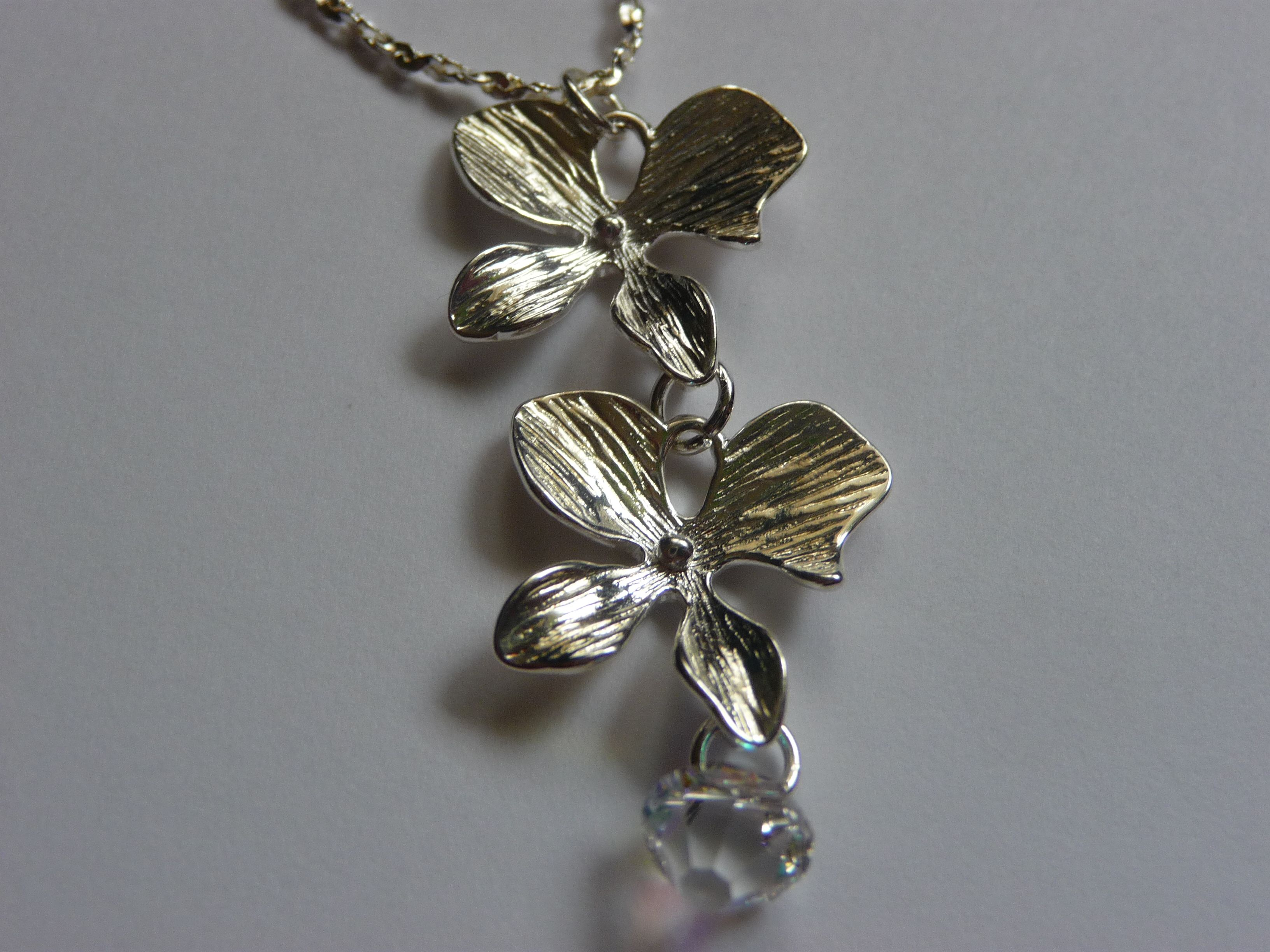 This lovely orchid design offers a beautiful Swarovski crystal for a little added sparkle to this dainty necklace. The two orchid charms are sterling silver plated and are hung from an 18 inch sterling silver plated chain. This necklace is easily worn casual or dressy.