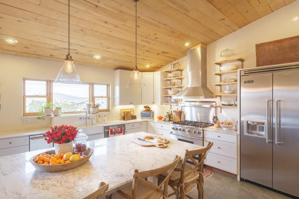 this light and bright eat in kitchen features wooden stools positioned around a gray and white on kitchen island ideas eat in id=42566