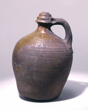 Watering-pot; red earthenware; oviform body; spreading rim with small orifice on top; perforated base; handle with trefoil ending; bright gr...