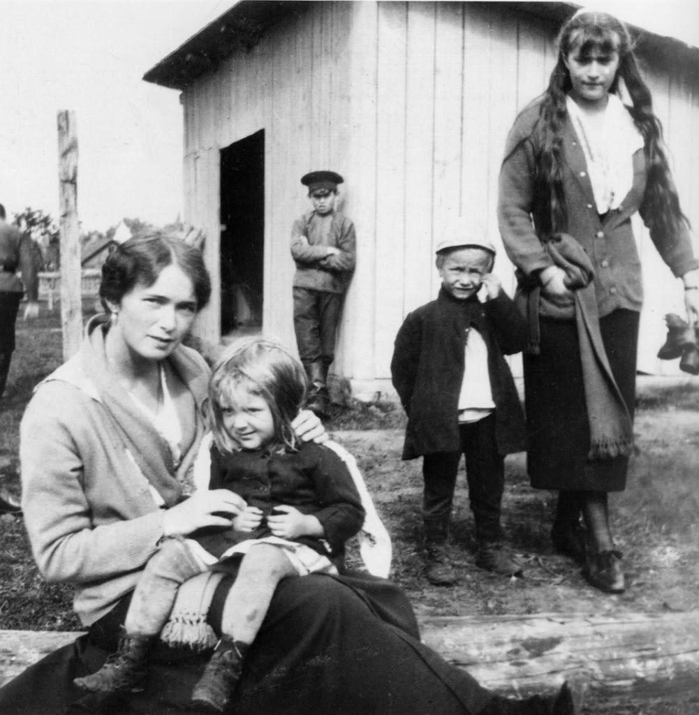 """Grã-duquesas Olga Nikolaevna da Rússia e Anastasia Nikolaevna da Rússia com crianças camponesas em uma estação de trem próximo à Mogilev. Grã-duquesa Olga segurando a menina """"Stephania"""" em seu colo, grã-duquesa Anastasia caminhando em direção à câmera com o menino """"Bolyus"""",  a criança de braços cruzados não é nomeado. Primavera de 1916."""