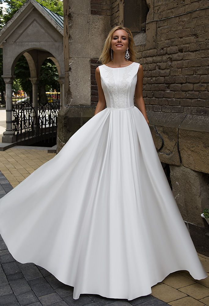 2523ffdd3c Romantic satin A line dress with a bateau neckline and covered back. Soft  folds of the A line skirt are pleated at the waistline. Secret pockets are  hidden ...