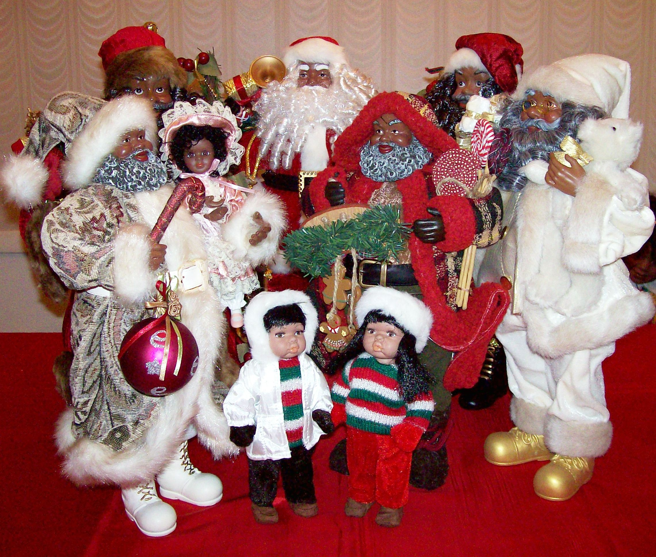 A gathering of various African American Santas and two doll