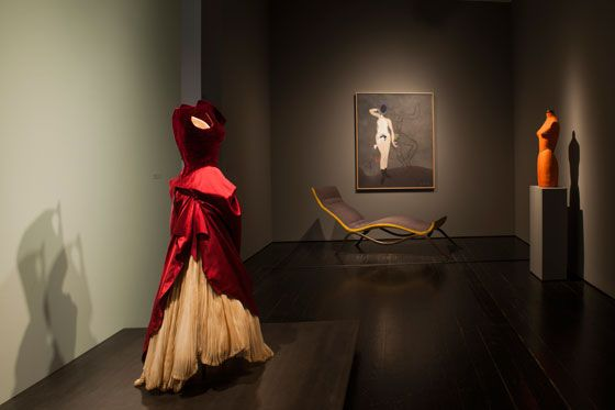 "The entrance to the exhibit ""A Thin Wall of Air: Charles James"" features James's red satin-and-velvet ball gown he designed for Dominique. He also did a version of this dress for Babe Paley and a select group of clients. The iron-framed yellow-and-gray chaise in the background is paired with Max Ernst's Retour de la belle jardinière. James's orange dress form for Dominique is on the right. It lived in her dressing room."