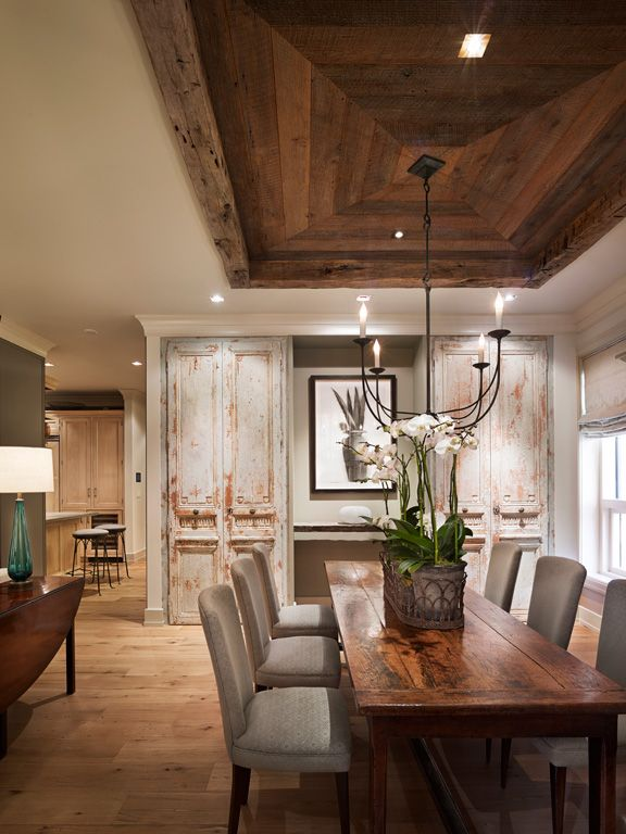 Love the open concept from dining to other areas and love the wood tray  ceiling as well as the beautiful aged cabinets!