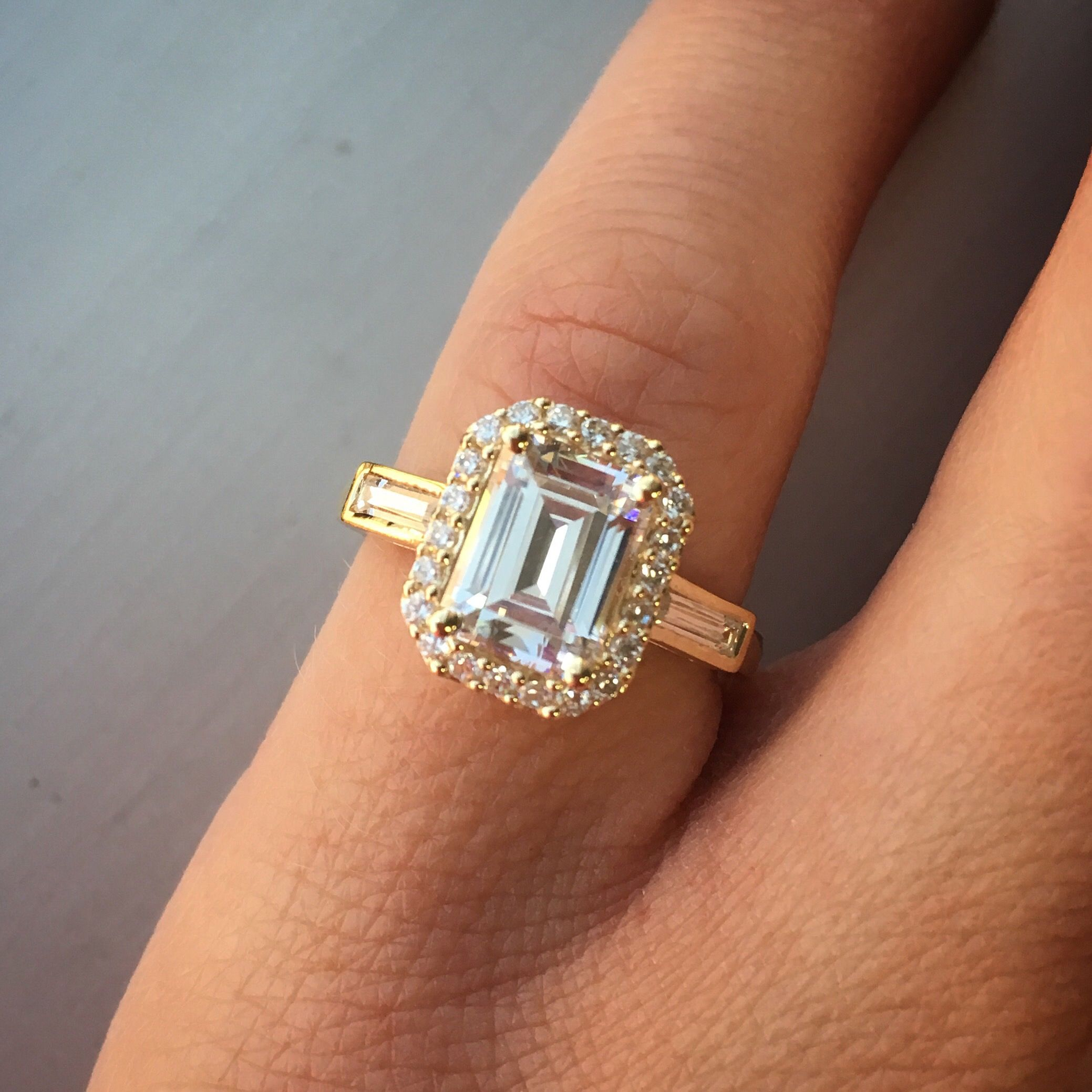 Emerald cut diamond engagement ring with pave diamond halo and