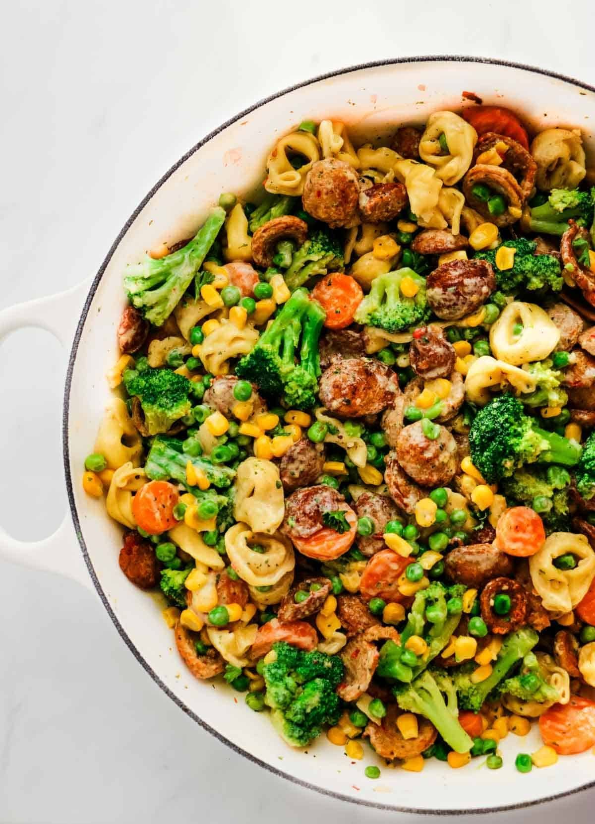 easy chicken recipes for dinner to feed your family? This easy chicken sausage pasta skillet meal is perfect! Just add veggies, tortellini and mix in a creamy garlic sauce for a crowd-pleasing dinner that can be prepared in under 30 minutes. | via  |