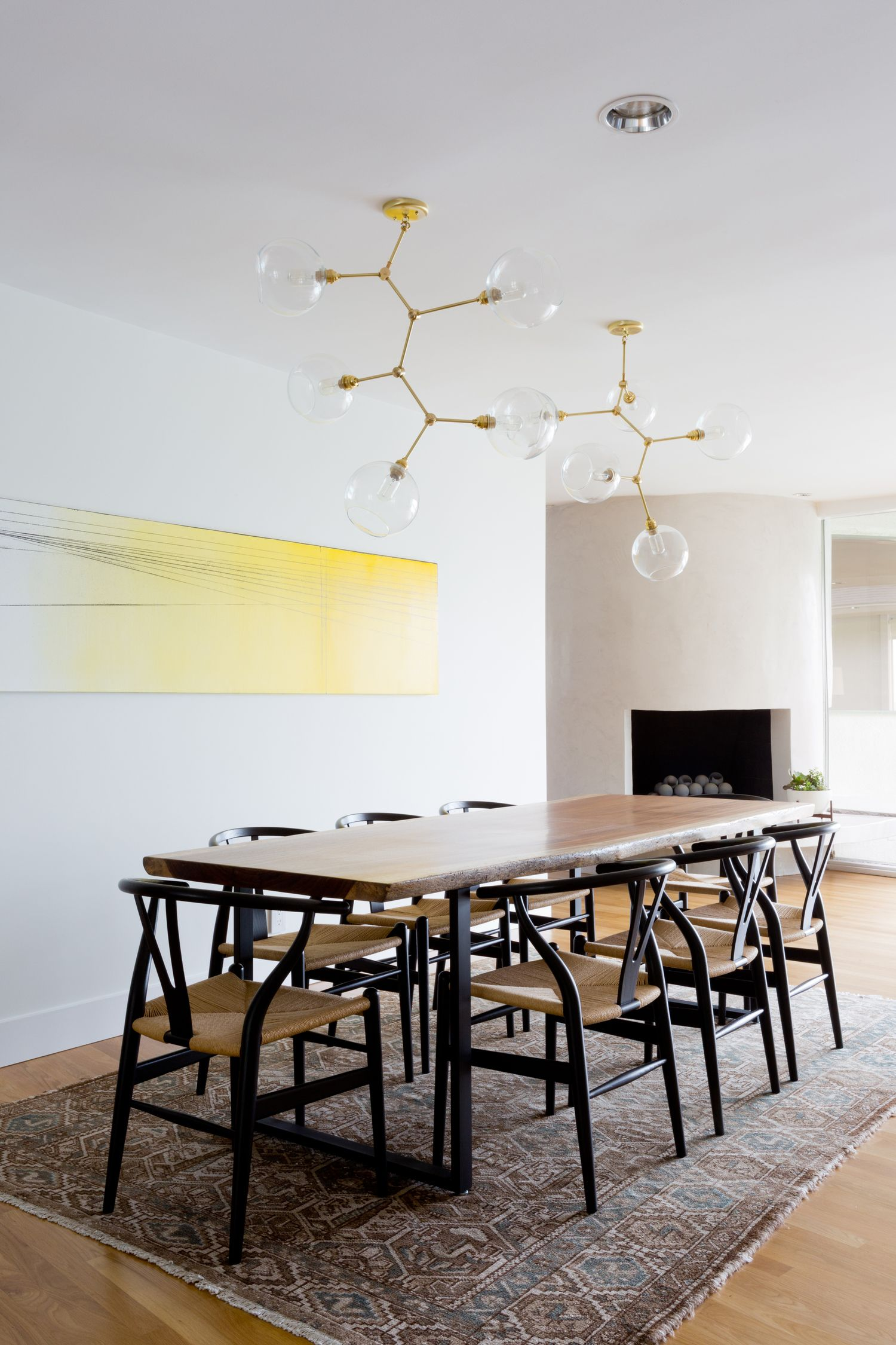 Earthy modern dining room with gold light fixture black wishbone