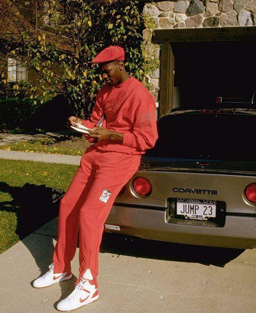 Michael Jordan leaning on a Corvette in a sweatsuit.