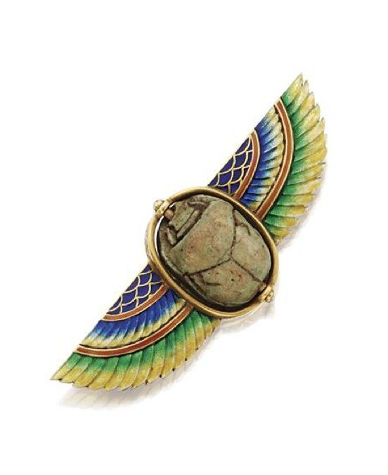 EGYPTIAN-REVIVAL GOLD, ENAMEL AND FAIENCE SCARAB BROOCH, MARCUS & CO., CIRCA 1900. The faience scarab flanked by a pair of wings applied with translucent yellow, green, orange and blue enamel, the reverse of the wings engraved with feathers, signed Marcus & Co.