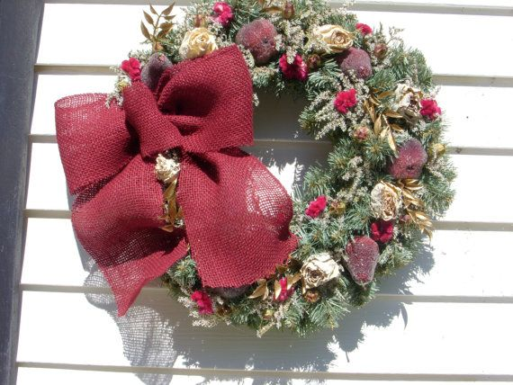 This beautiful Christmas wreath measures a large 18 and features a large red burlap bow. It is made on a pine wreath and is filled with