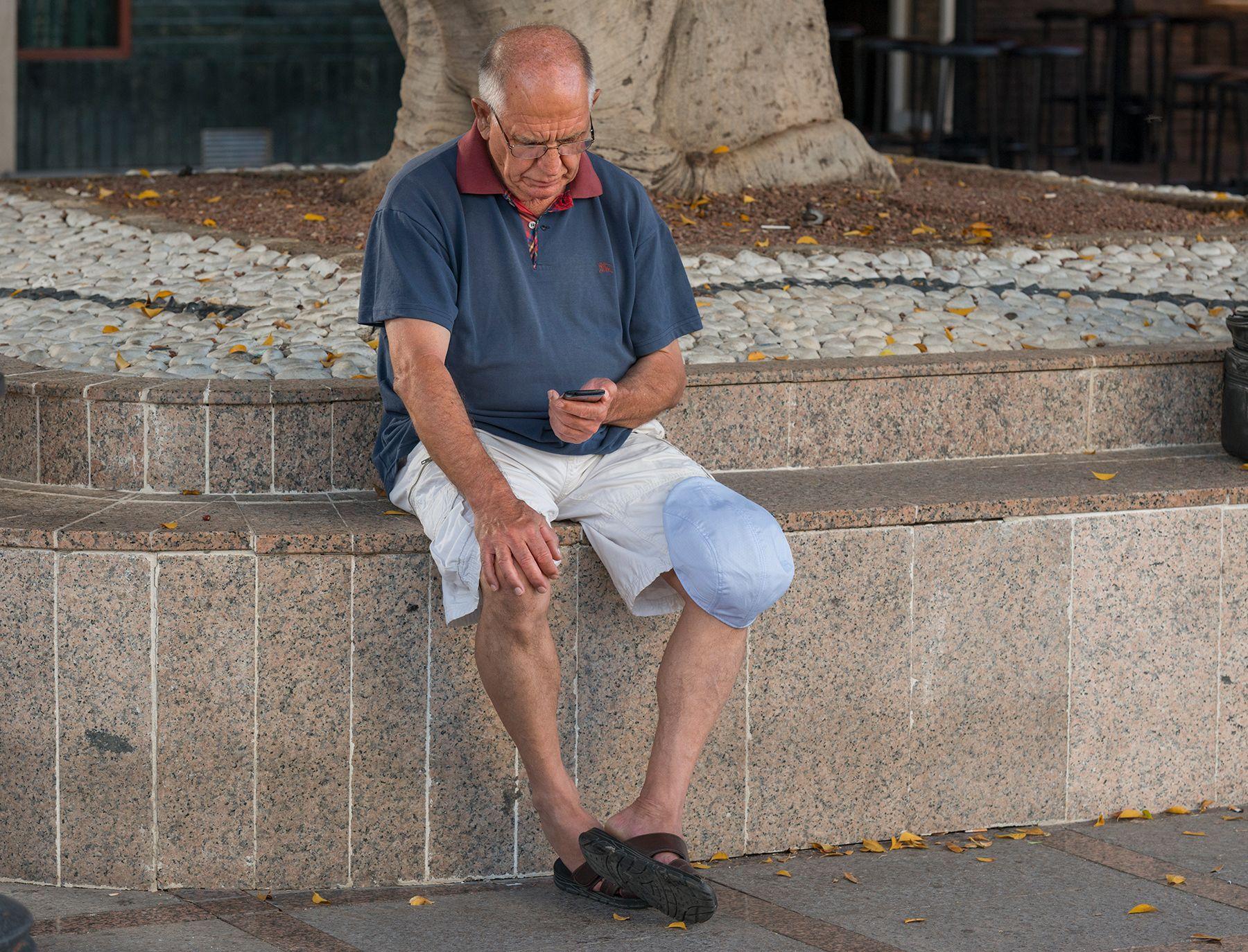 Hombre con alopecia androgénica mirando el móvil