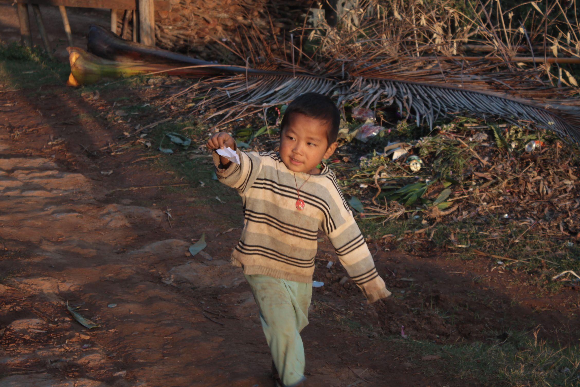 Niño jugando con un avión de papel