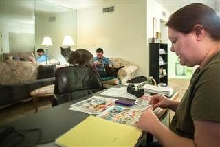 Erika Trowell organizes her coupon collection at home in Phoenix, Ariz., while her husband, Ben, reads a book. Trowell estimates that she saves between $30 and $50 per month by using coupons.