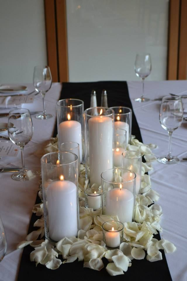 Romantic Candles Clustered In A Bed Of White Rose Petals For A Long Table Centerpiece Candle Wedding Centerpieces Rose Petal Candle Wedding Centerpieces