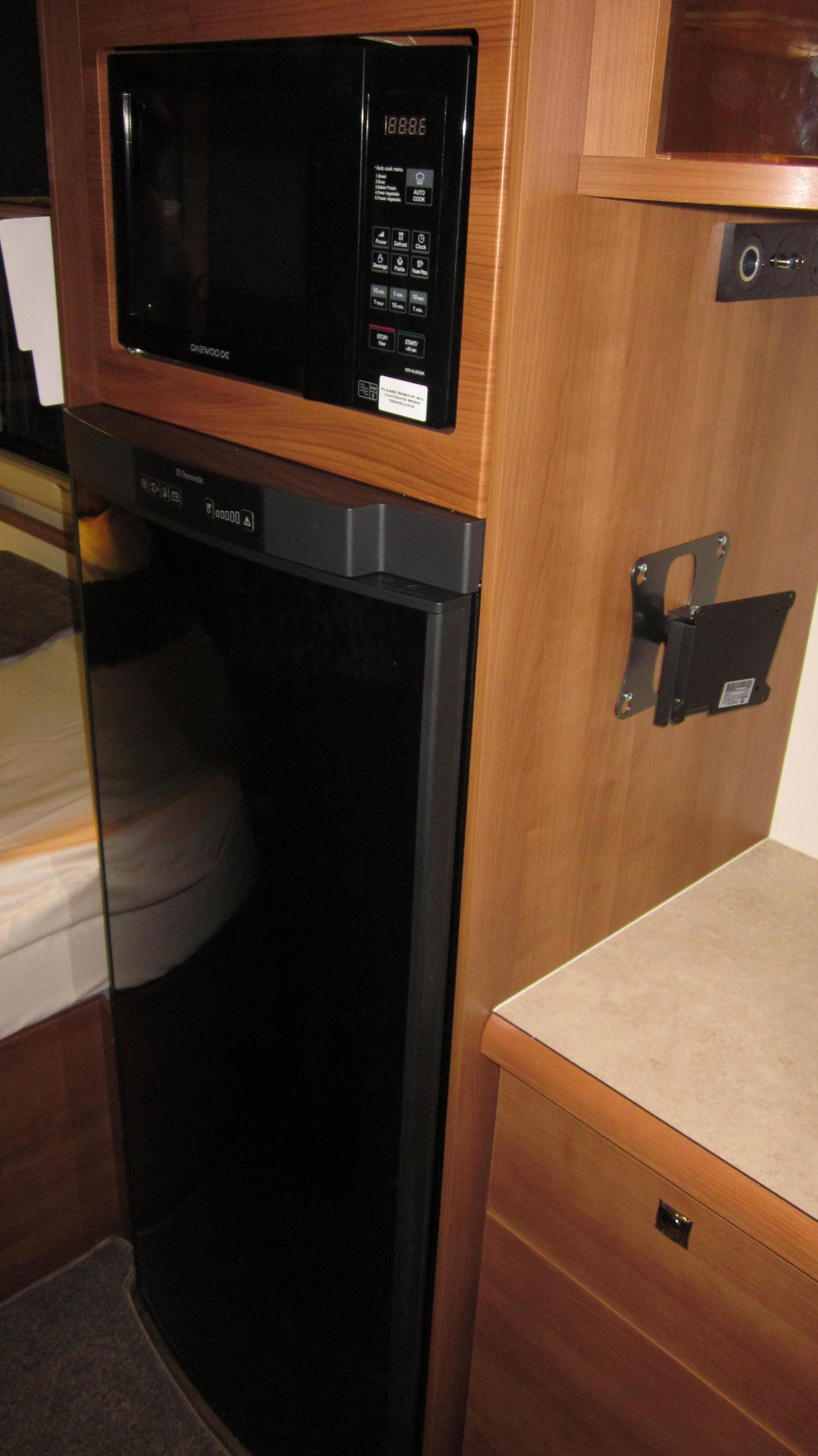 Full Size Fridge Freezer Above Is Microwave Oven To Side You Can See Tv Mountings And Small Cupboard Below