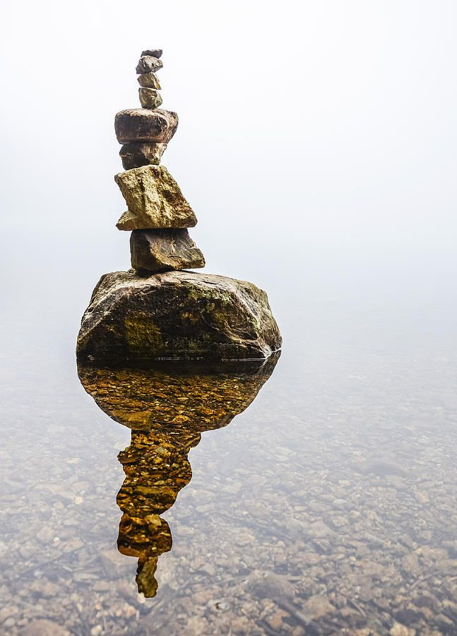 Cairn in Fog A shot of a cairn in a fog covered lake. fog alpine lake cairn