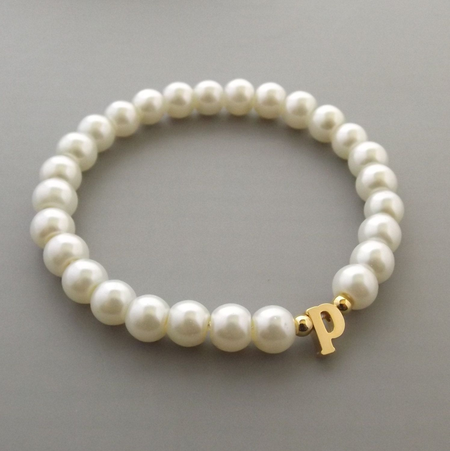 Gold lowercase initial bracelet on stretch cord baby pearls gold