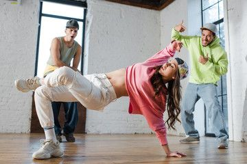 selective focus of stylish girl breakdancing near ...