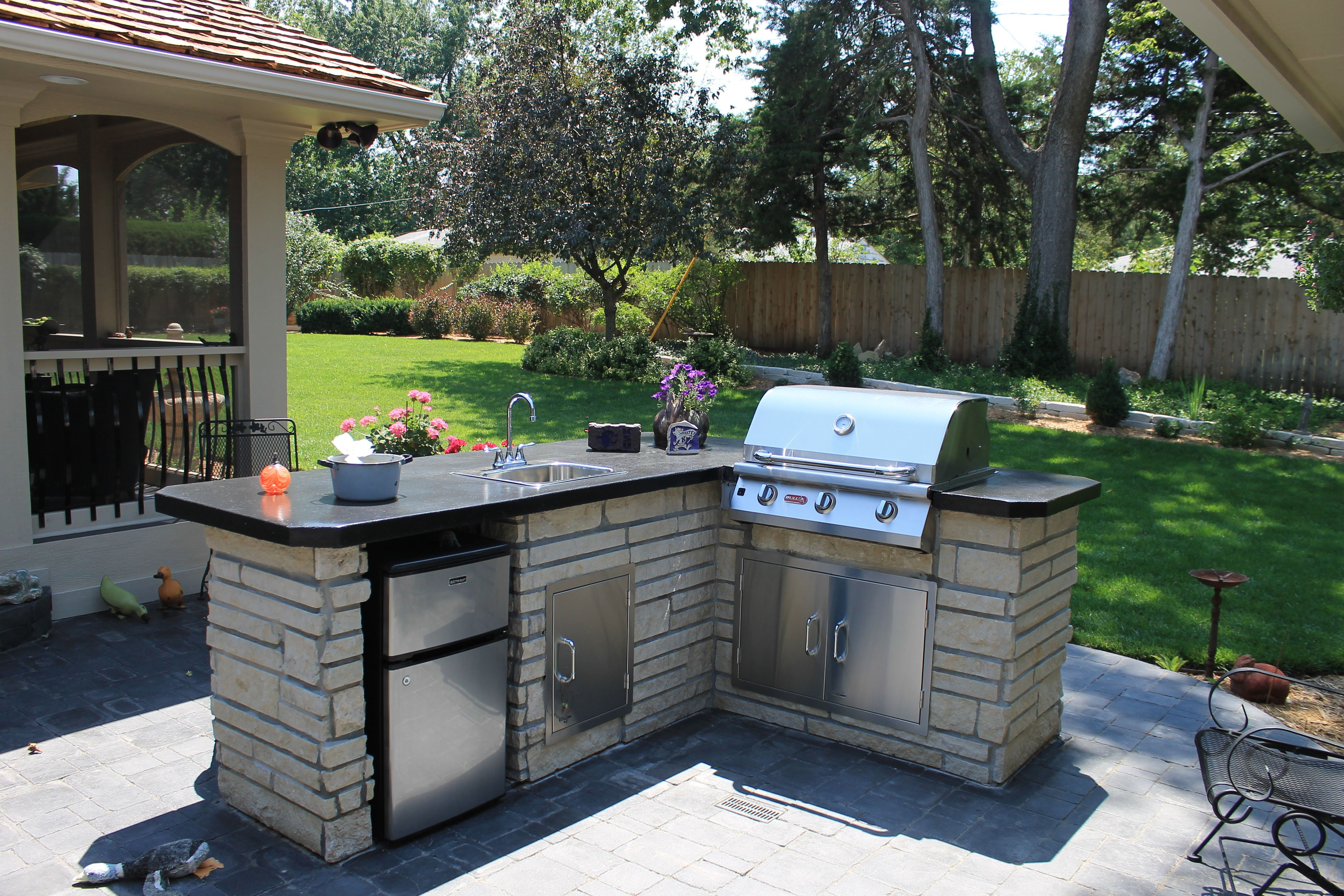 Poured concrete top with a sink and grill in set. Natural gas is hooked up to the grill.