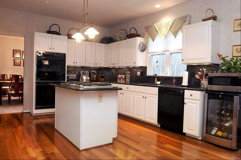 kitchen with white cabinets and black appliances google