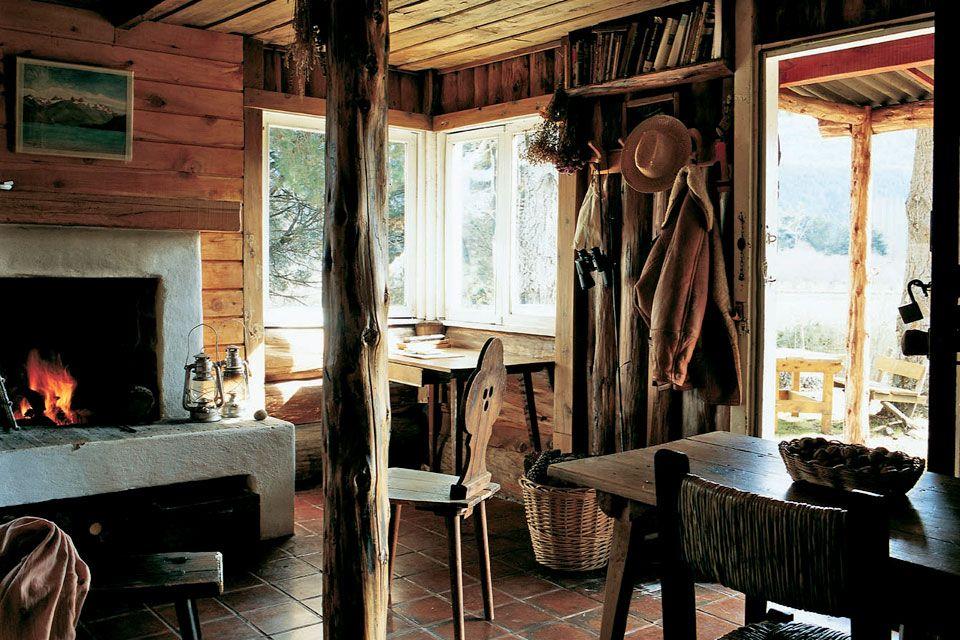 Living comedor en una cabaña de la Patagonia argentina. Silla estilo alpino y grueso tronco de ciprés sosteniendo el cielo raso.
