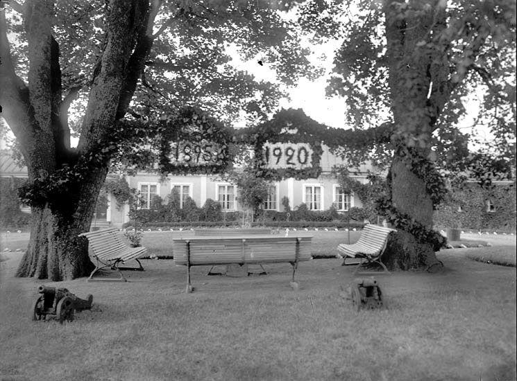 """En vy mellan två ekträd, och några parksoffor  med några små salutkanoner framför.  Mellan träden hänger ett slags girlander med årtalen """"1895""""  och """"1920"""".  I bakgrunden skymtar huvudbyggnaden på Gårdsby."""