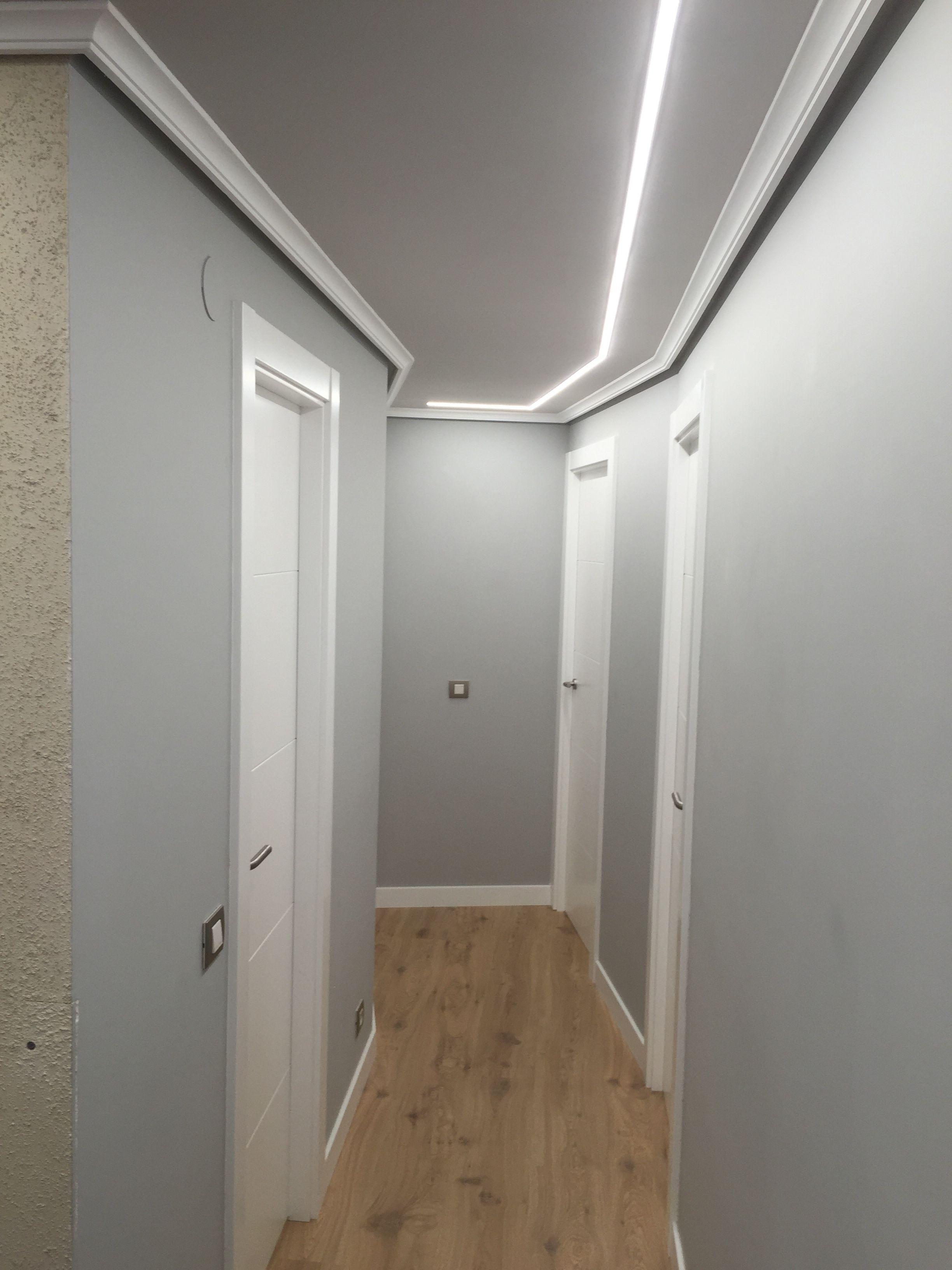 Pasillo iluminado con tiras de LEDs empotradas en el techo