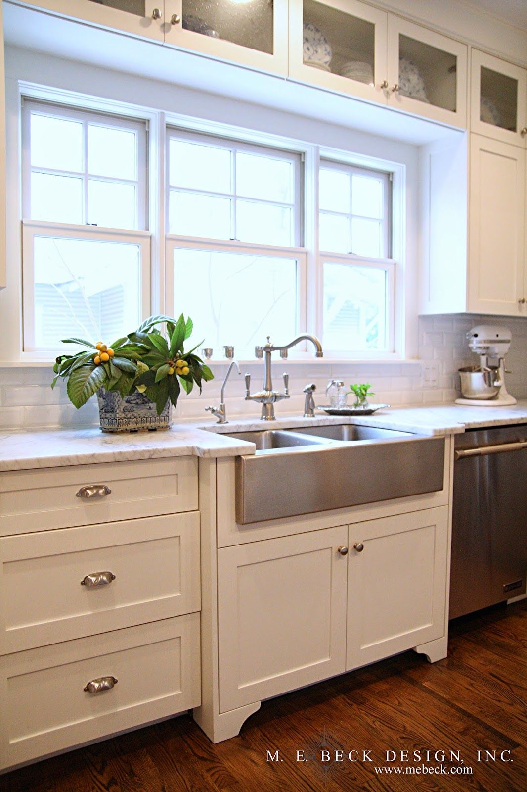 Kitchen backsplash near window  lit glass front cabinets above windows instead of fixed transom