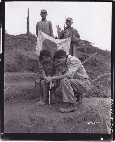 """An soldier gives a liberated Japanese comfort women first aid as two Chinese Nationalist soldiers stand behind him, displaying a captured Japanese flag."""