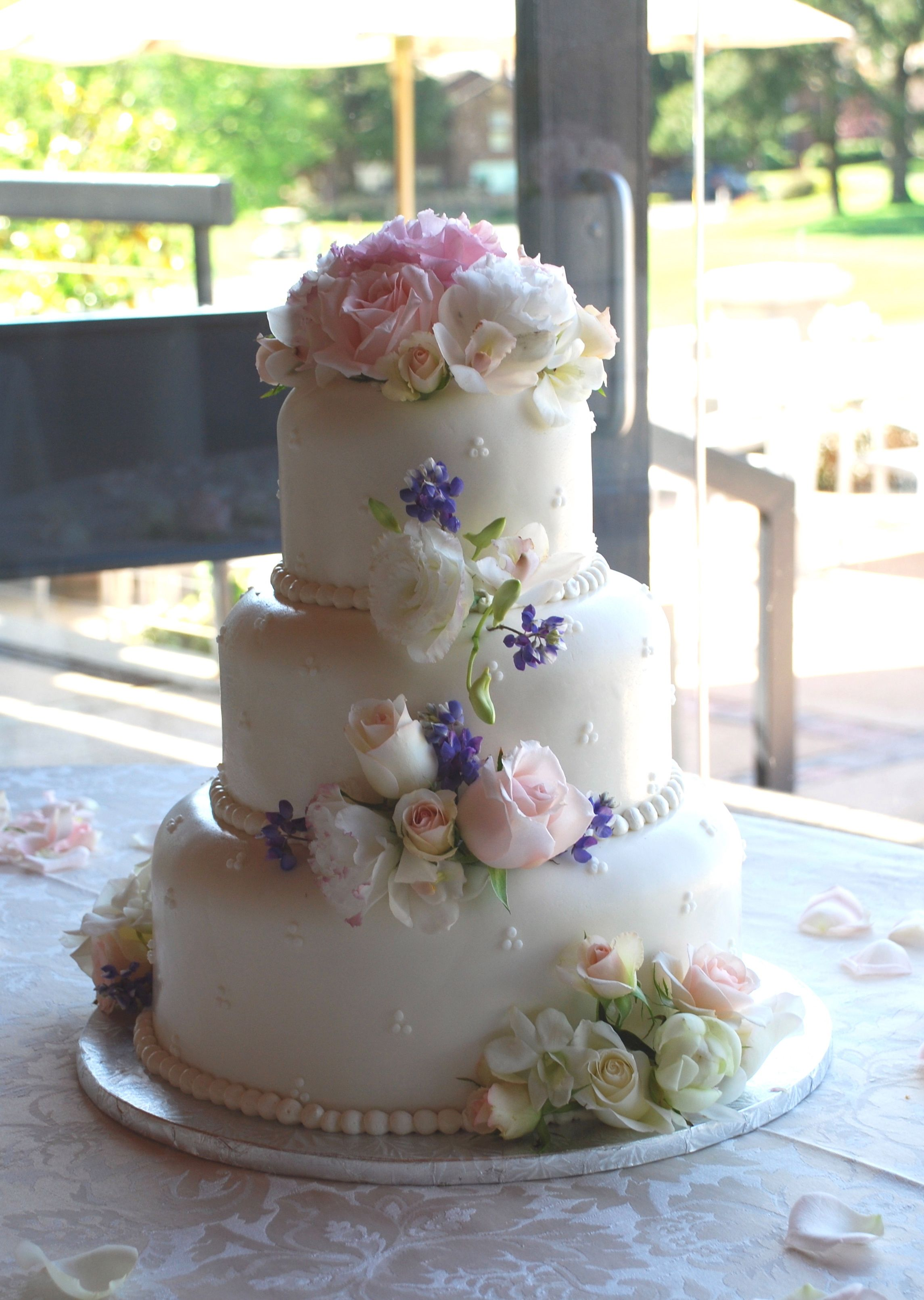 Romantic cake decoration with roses, lisianthus, orchids, and  blue lupine.