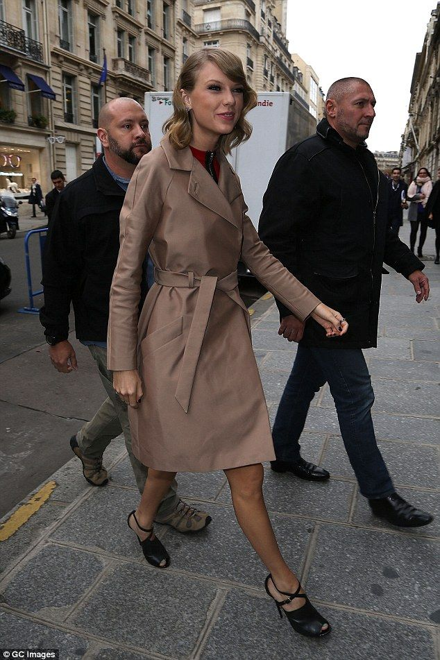 Keeping cosy... The 24-year-old rugged up in a caramel-coloured trenchcoat which showed off her toned legs
