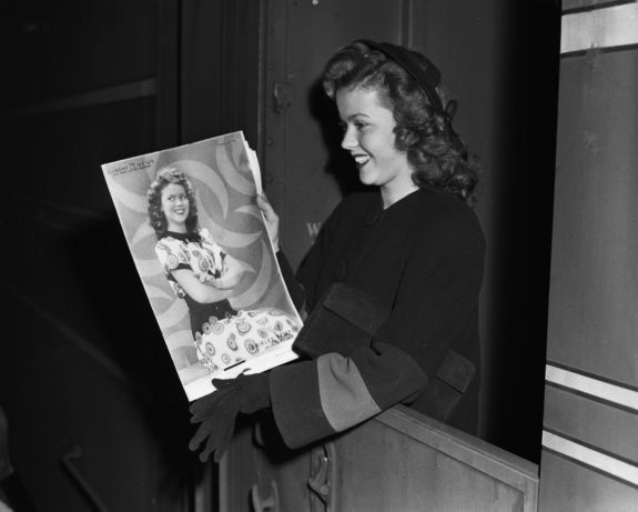 Shirley Temple, arriving here on the 20th Century to start War Bond tour, looks at portrait of herself in the Sunday News color roto, 1944.