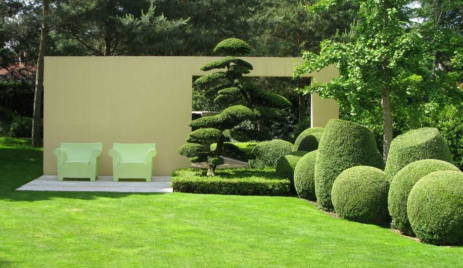 modern garden with a seating place in front of a screening the window in the wall adds interest. Black Bedroom Furniture Sets. Home Design Ideas