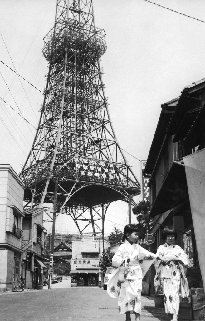 Two young girls in kimono in a street near the almost completed Tokyo Tower - July 1958